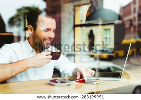 Young happy man at cafe using smartphone and drinking coffee - stock photo