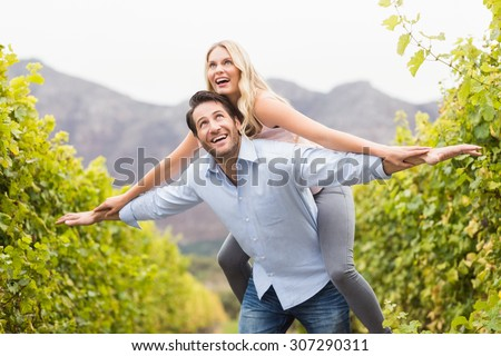 Young happy man carrying happy woman on his back in the grape fields