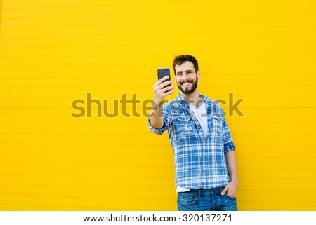 young happy man casual dressed with headphones and smart phone on yellow background - stock photo