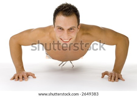 Young happy man doing push up exercise. White background in studio.