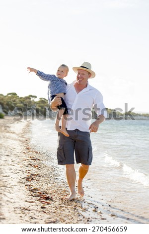 young happy man father of sweet blond little girl holding his daughter hand taking a walk on beach sea shore on a sunny summer day enjoying together playing with sand and water - stock photo