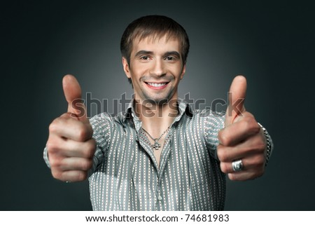 Young happy man going thumbs up