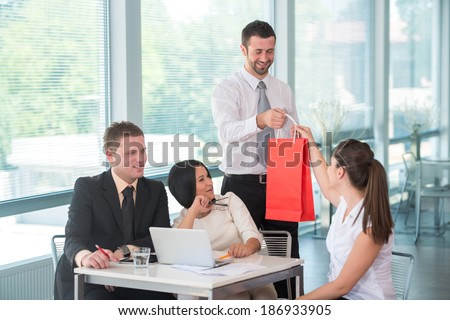 Young happy man handing a red paper bag to a female colleague in office - stock photo