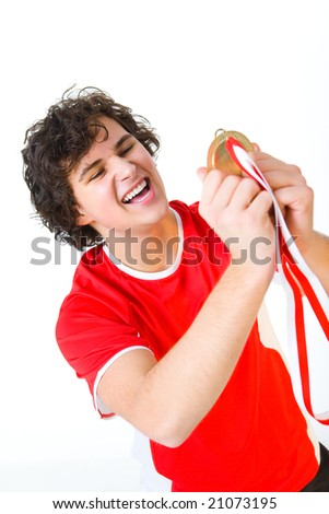 Young happy man holding golden medal. Front view. - stock photo