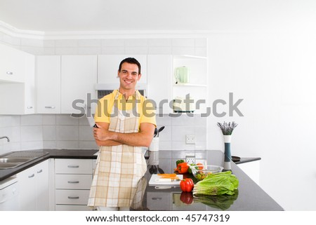 young happy man in a modern kitchen - stock photo