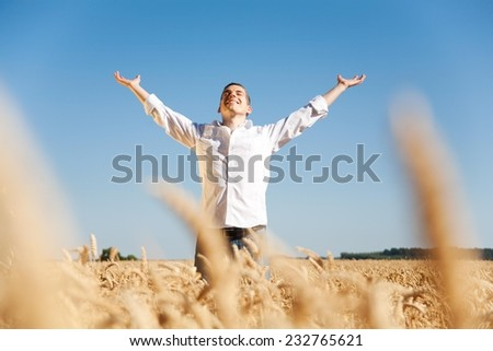 Young happy man in a wheat field. - stock photo