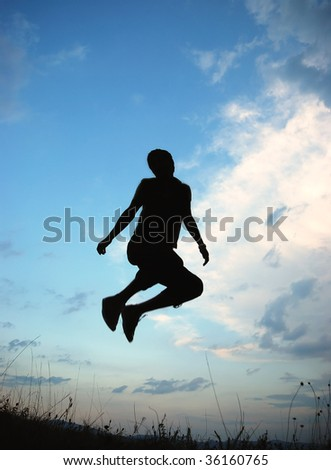 Young happy man is jumping on green meadow - stock photo