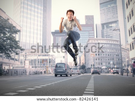 Young happy man jumping on a city street - stock photo