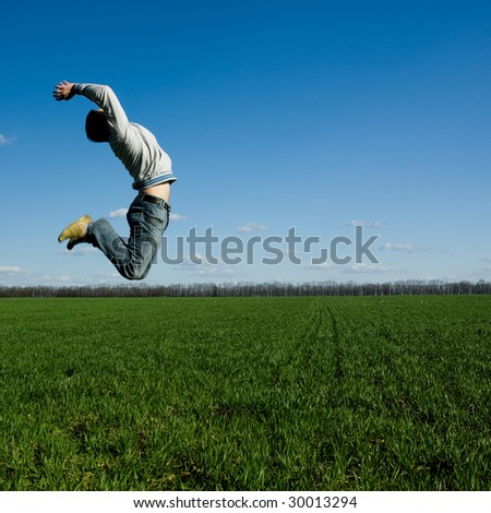 young happy man jumping on the green field - stock photo