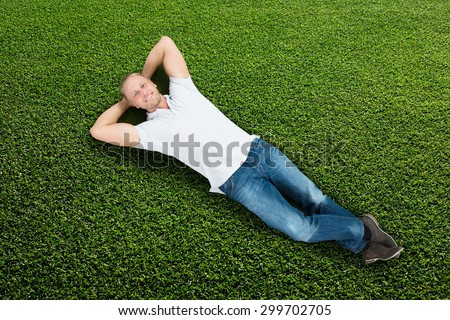 Young Happy Man Lying On Green Grass - stock photo