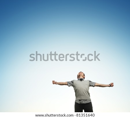 Young happy man on blue sky background with raising hands and looking to a sky - stock photo
