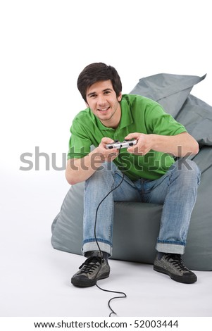 Young happy man playing video game with control pad on white background - stock photo