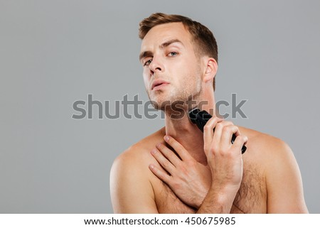 Young happy man shaving with electric razor isolated on the gray background - stock photo