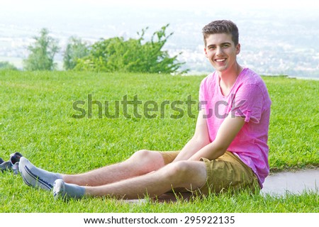 Young, happy man sitting on a meadow