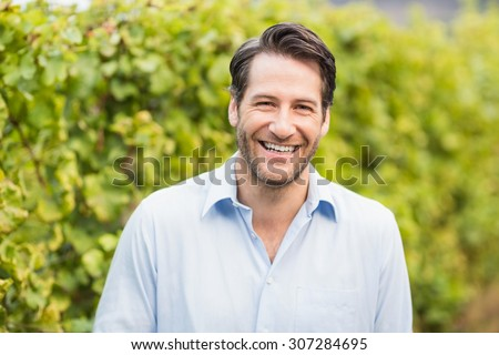 Young happy man smiling at camera in the grape fields - stock photo