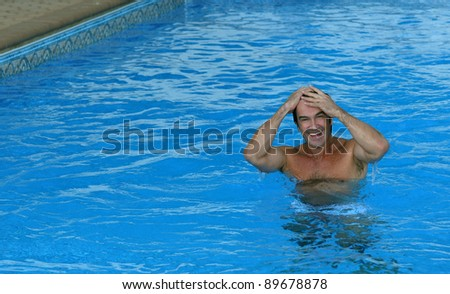 Young happy man smiling on a pool with clear blue water