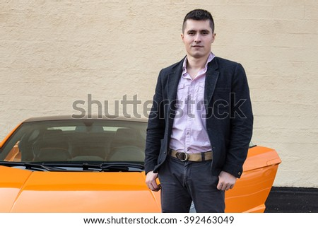 Young happy man standing near luxury sport car against the wall on the outdoors parking lot