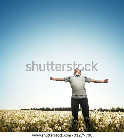 Young happy man standing on a meadow with raising hands and looking to a sky - stock photo