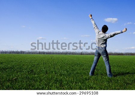 young happy man standing on the green field - stock photo
