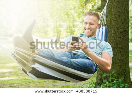 Young Happy Man Using Mobile Phone While Relaxing In Hammock At Garden - stock photo