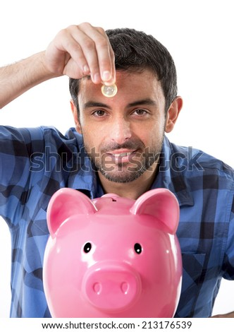 young happy man wearing casual shirt holding coin putting it into pink piggy bank in saving money , financial and banking concept  isolated on white background - stock photo