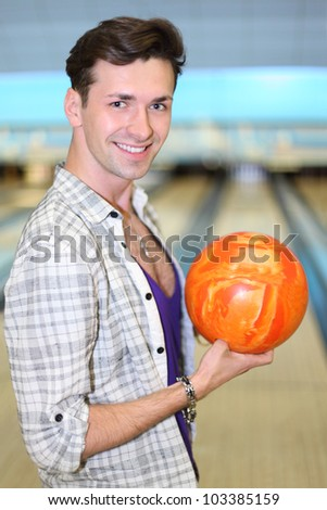 Young happy man wearing in white checkered shirt holds orange ball in bowling club; shallow depth of field