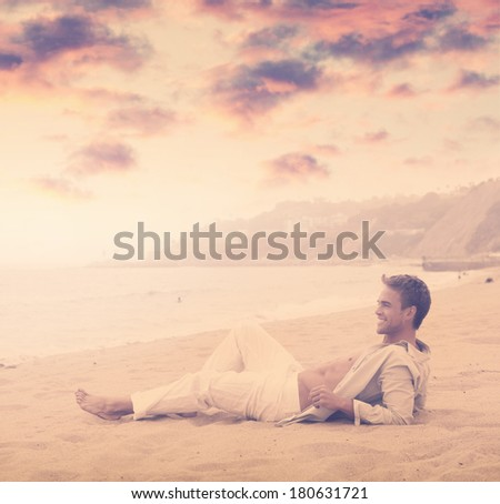Young happy man with great smile on the beach with dramatic sky and overall vintage toning and styling - stock photo