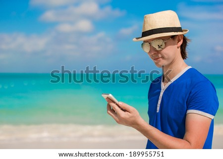 Young happy man with his phone on beach vacation - stock photo