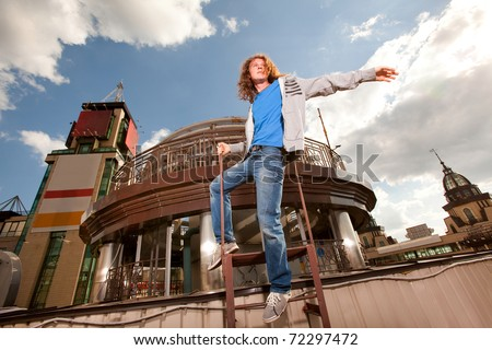 Young happy man with long hair, sky and metal structure on background
