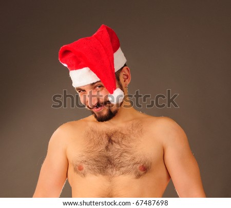 Young happy man with naked torso in Santa hat.