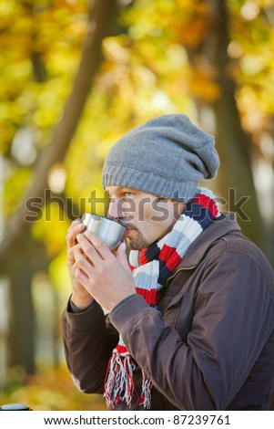 Young happy man with scarf and hat drinks tea in autumn park. Vertical view
