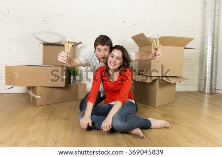 young happy married couple sitting on flat floor unpacking cardboard boxes celebrating with champagne toast moving in new home apartment smiling happy in real estate concept