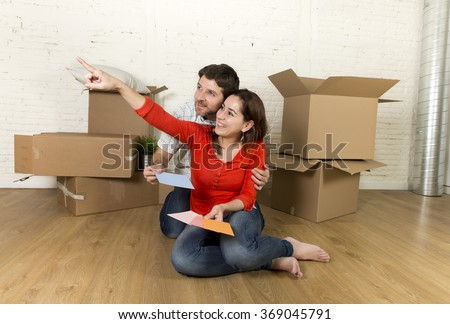 young happy married couple sitting on flat floor unpacking cardboard boxes moving in new home apartment smiling happy with color chart planning for decoration of the house in real estate concept