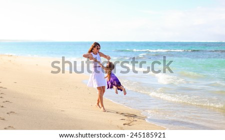 Young happy mother and adorable daughter having fun at exotic beach on sunny day