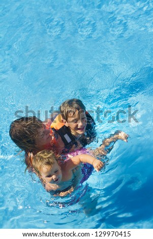 young happy mother and children enjoying vacation in swimming pool - stock photo