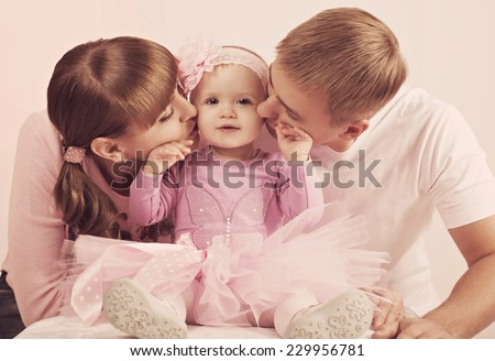 Young happy mother and father with baby girl