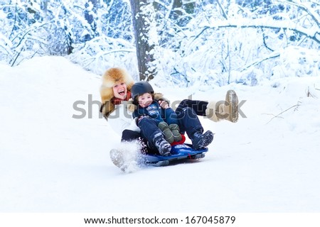 Young happy mother and her adorable son having fun together on a sleigh ride in a snowy forest - stock photo