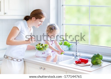 Young happy mother and her cute curly toddler daughter washing vegetables together in a kitchen sink getting ready to cook salad for lunch in a sunny white kitchen with a big garden view window - stock photo