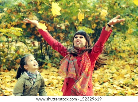 Young happy mother and her daughter play in autumn park - stock photo