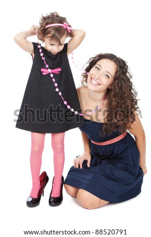 Young happy mother and her funny little girl in mummy's shoes over white