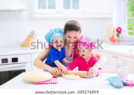 Young happy mother and her kids, adorable toddler girl and a little funny baby boy wearing pink and blue chef hats baking a pie together in a white sunny kitchen with big window - stock photo