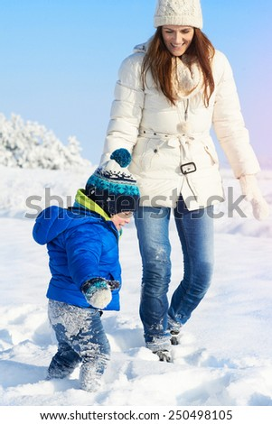 Young happy mother and her little toddler baby boy enjoying walk in a beautiful snowy winter sunny day - stock photo