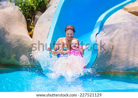 Young happy mother and two children, baby boy and toddler girl having fun at water slide in a tropical pool on a hot summer day - stock photo
