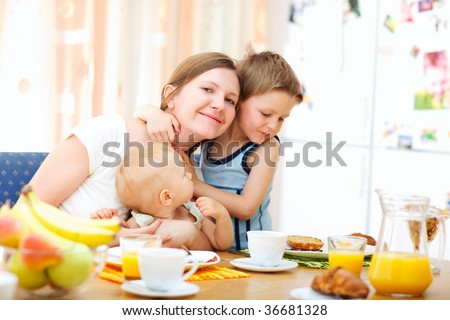Young happy mother and two kids having breakfast together - stock photo
