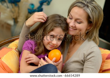 young happy mother embracing her daughter - stock photo