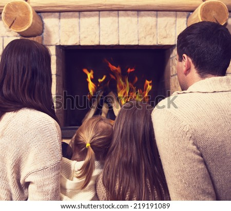 Young happy mother, father and two daughters by a fireplace on Christmas - stock photo
