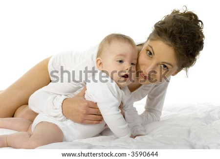 Young happy mother holding baby. Woman is lying in bed, holding baby. White background, looking at camera