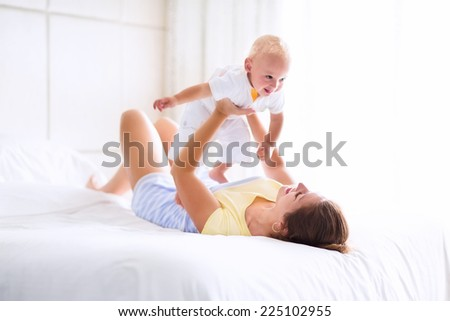 Young happy mother holding her adorable baby, cute blond curly boy, playing in a white bed enjoying a sunny morning in a modern home bedroom - stock photo