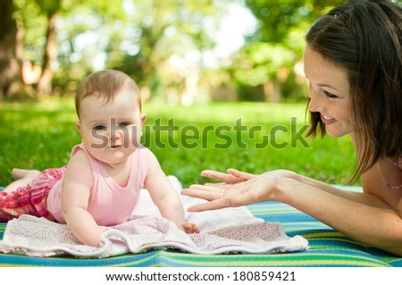Young happy mother playing with her baby - outdoor in nature - stock photo