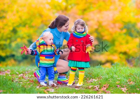 Young happy mother playing with her children, cute baby boy and adorable toddler girl wearing colorful rainbow jackets, having fun in a beautiful autumn park with yellow maple trees - stock photo